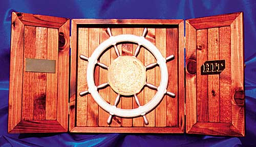 Photograph of ships wheel in a presentation box